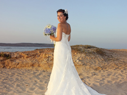 The bride having a stroll on the sandy beach after the civil wedding