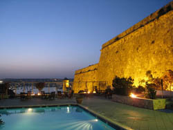 Lit up pool area with view of the Bastions